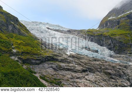 Detail Shot Of Boyabreen Glacier Flowing Down The Rocky Mountain. Norwegian Landscape On A Day Of Su