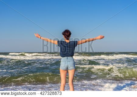 Tween Slender Girl Standing On Sand Beach Of Sea Coast Against Stormy Waves In Sunny Summer Day. You