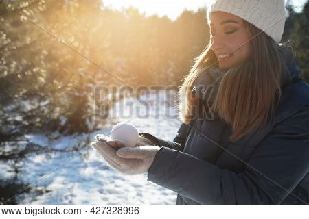 Woman Holding Snowball Outdoors On Winter Day, Space For Text