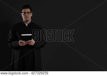 Priest With Bible On Black Background. Space For Text
