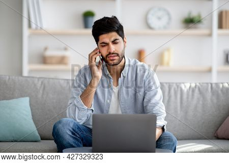 Remote Business. Concerned Arab Freelancer Talking On Cellphone And Using Laptop Computer, Sitting O