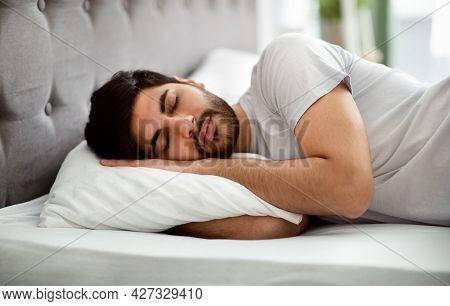 Comfortable Sleep. Millennial Arab Man Sleeping Peacefully And See Sweet Dreams, Lying In Comfy Bed