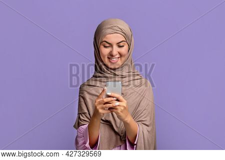Cool Application. Excited Young Muslim Woman In Hijab Using Smartphone, Texting Or Browsing Internet