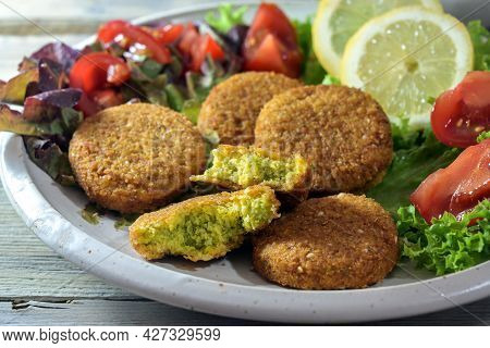 Vegetarian Falafel From Spiced Chickpeas With Salad Of Lettuce, Tomatoes And Lemon Slices On A Plate