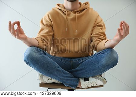 Man Meditating In Office Chair Against Light Background, Closeup