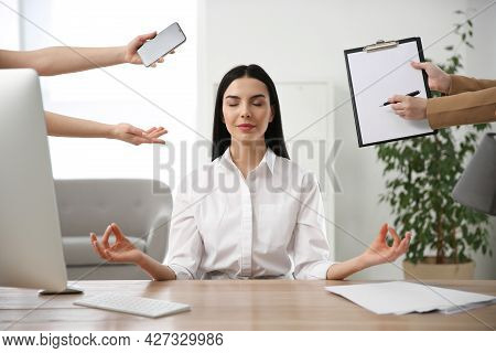 Overwhelmed Woman Meditating At Workplace. Stress Relief Exercise