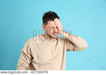 Man Suffering From Terrible Migraine On Light Blue Background