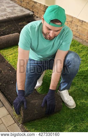 Worker Laying Grass Sod On Ground At Backyard