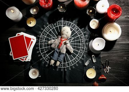 Voodoo Doll Pierced With Needle Surrounded By Ceremonial Items On Table, Flat Lay