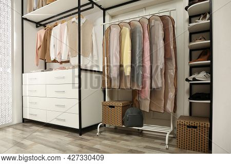 Garment Bags With Clothes On Rack In Dressing Room