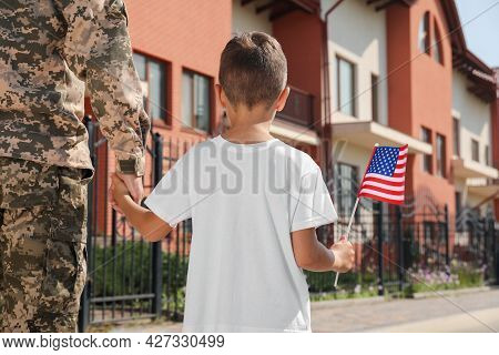 Soldier And His Little Son With American Flag Outdoors, Back View. Veterans Day In Usa