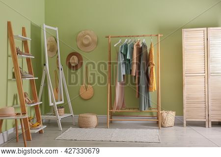 Modern Dressing Room Interior With Clothing Rack And Mirror Near Light Green Wall