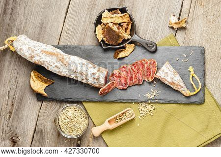 Above Photo Of Sliced Salami Sausage With Dried Slices Of Porcini Mushrooms And Fennel Herb On Woode