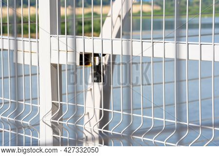 Double Metal Fence Of The River Fence, A Summer Sunny Day, The Background Is Very Blurred. A Territo