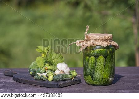 Fresh And Salted, Pickled Green Cucumbers In A Glass Jar On An Old Wooden Table In The Summer Garden