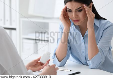 Young Woman Suffering From Migraine In Hospital, Closeup