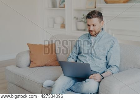 Attentive Handsome Young Man In Casual Clothes Using Laptop During Leisure Time While Sitting On Sof