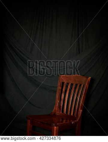 Inside Studio Image Of Draped Black Cloth Background With Red Wooden Chair, With Plenty Of Copy Spac