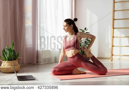 Attractive Young Woman Doing Stretching Online At Home Under Guidance Of Professional Trainer Online
