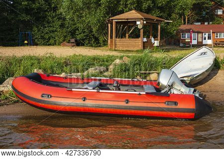 Red Inflatable Rubber Boat With A Motor Near The Lake Shore, Fishing, Tourism, Active Recreation.