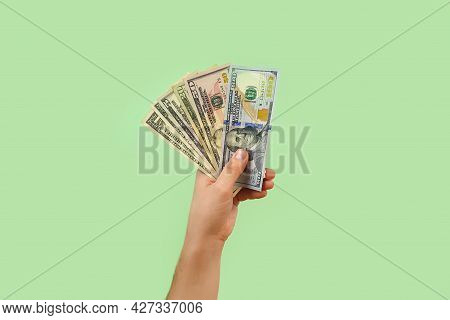 Male Hand Holds Dollar Bills, American Money On Green Background. Top View