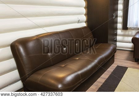 Brown Leather Sofa In The Interior Of A Wooden Country House. The Interior Of The Living Room. Vacat