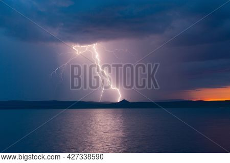 Bright Lightning Strike During A Thunderstorm In The Twilight Stormy Sky Over The Water Of The Lake
