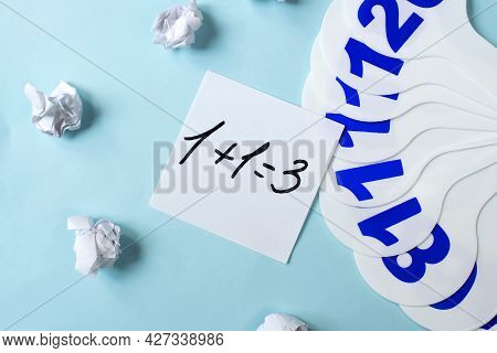 On A Blue Background Next To A Plastic Fan With Numbers And Crumpled Sheets Of Paper There Is A Shee