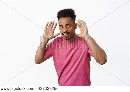 Intrigued African American Man Trying To Overhear Gossip, Holding Hands Near Ears And Looking Sidewa