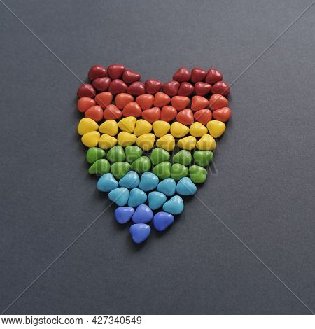 Big Heart Of Small Colored Candy In Form Of Hearts Like Lgbt Flag On Gray Background. Lgbt And Human