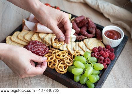 Party Cooking, Female Hands Laying The Mini Pretzel On Charcuterie Board With Sausage, Fruit, Cracke