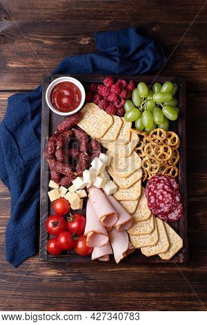 Charcuterie Board With Sausage, Crackers, Fruit And Cheese On A Dark Wooden Background, Close-up.
