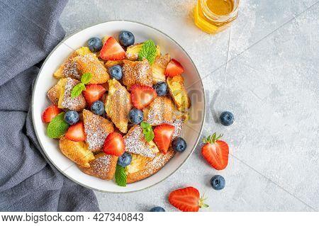 Kaiserschmarrn - Traditional Austrian Pancake Dessert With Fresh Berries And Powdered Sugar On A Gra