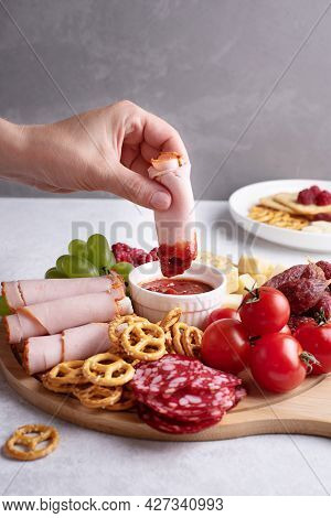 Plates With Appetizer, Female Hand Dipping A Slice Of Ham In Sauce On Round Charcuterie Board With S