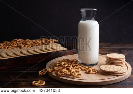 Breakfast And Snack Milk Bottle With Cookies And Mini Salted Pretzels On A Dark Wooden Background, C