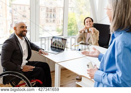 Multiracial colleagues discussing project while working at office