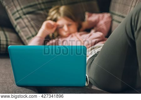 Teenage Girl With Laptop Lying On Couch, Watching Favorite Series