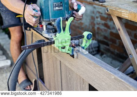 Densely Works With A Milling Machine On The Wooden Surface Of The Door. Professional Tools For Woodw