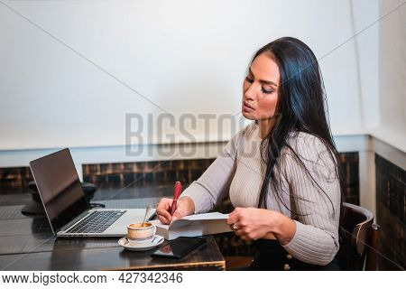 Brunette Girl Teleworking In A Coffee Shop With Laptop