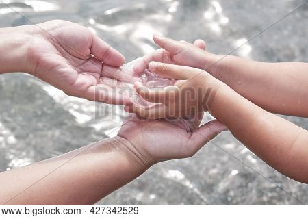 Childs Hands Giving Carefully Into Hand Of Mother Small Transparent Jellyfish Over Background Of Wat