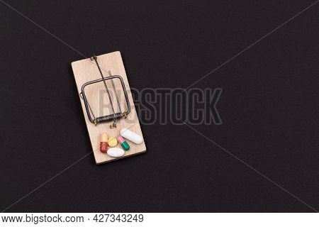 Pharmaceutical Addiction Or Big Pharma Trap - Colored Pills Or Capsules In Wooden Mousetrap On Black