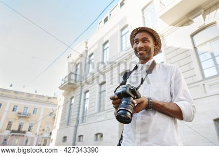 Black man with digital camera standing in european city. Young smiling guy wear straw hat, white shirt and wristwatch. Concept of travelling. Idea of freelance work. Sunny daytime
