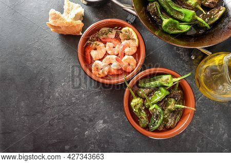 Spanish Tapa Bowls With Fried Pimientos Or Padron Peppers And Shrimps With Lemon And Herbs On A Gray