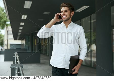 Pleased european businessman talking on mobile phone and holding documents. Young man standing on background of modern office building in city. Smiling bearded guy wear white shirt and jeans. Daytime