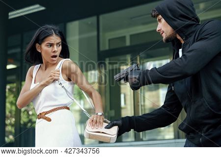 Angry robber want to steal handbag of frightened girl. Male bandit wear black hoodie and threatening with pistol to young european brunette woman. Concept of robbery. City daytime