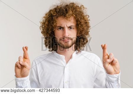 Young curly man with ginger hair holding fingers crossed for good luck isolated over white background