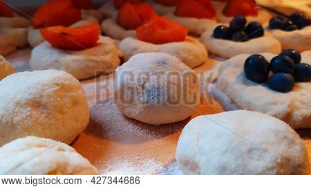 Close-up View Of The Preparation Of Traditional Blueberry Dumplings On A Rolling Board, In The Backg