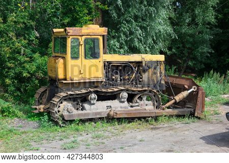 Old bulldozer on the background of trees