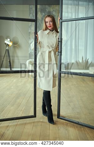 Autumn, spring style. Full length portrait of a gorgeous young woman posing in elegant white felt coat in modern apartments. Fashion and beauty shot.