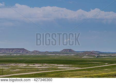 Badlands National Park, Sd, Usa - June 1, 2008: Table Hills On Horizon Above Green Prairie Under Blu